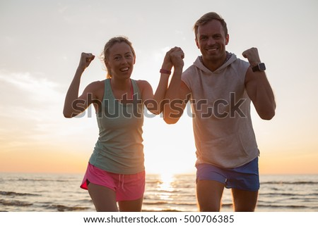 Happy couple after workout on the beach