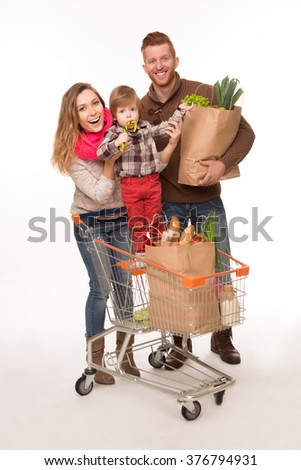 Happy couple and a baby posing over white background with shopping bags and shopping cart full of products. - stock photo