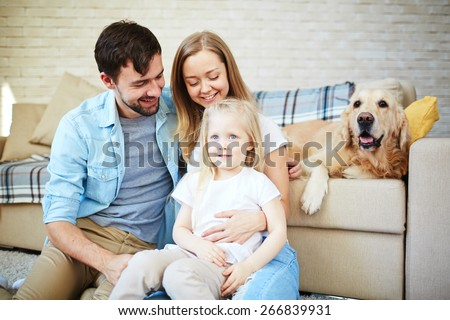Happy couple and their daughter enjoying home rest with pet on background - stock photo