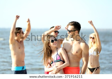 Happy couple and their playful friends relaxing at the beach, outdoors - stock photo