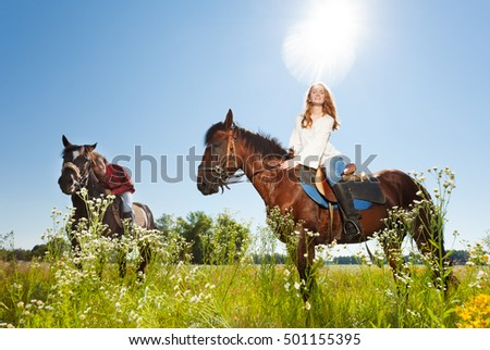 Happy couple and their stallions in flowery meadow