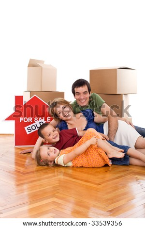 Happy couple and two kids laying on the floor of their new home, with cardboard boxes - isolated - stock photo