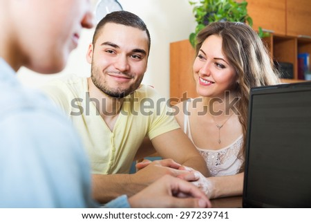 Happy couple answer questions of social worker at home