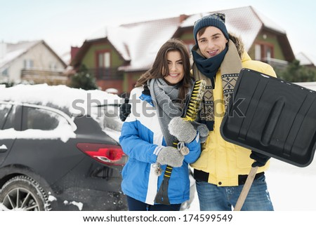 Happy couple are ready to cleaning car from snow - stock photo