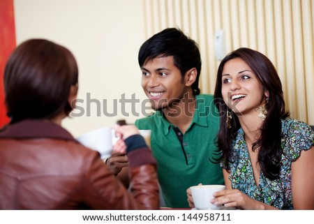 Happy couple at a cafe talking with friends - stock photo