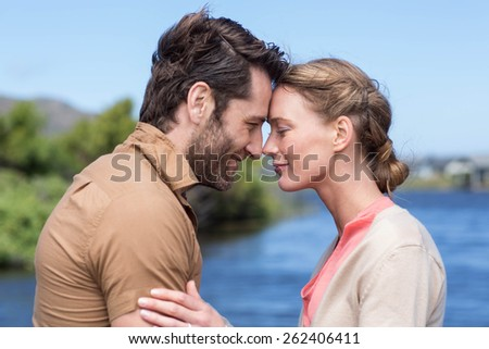 Happy couple at a lake in the countryside - stock photo