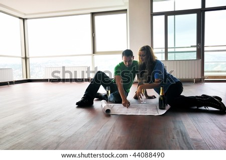 happy couple at big bright comfort apartment celebrate with glasses of champagne - stock photo
