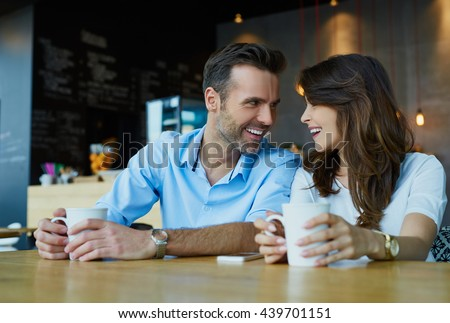 Happy couple at coffee shop looking at each other