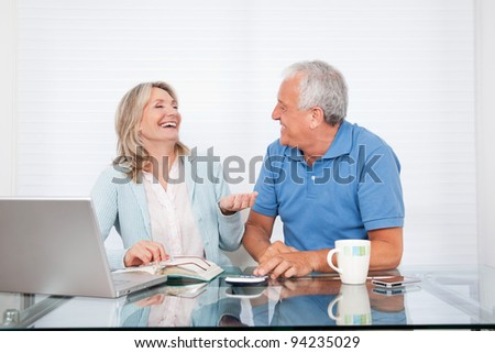 Happy couple at dining table working on laptop on house finance - stock photo