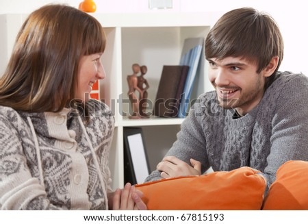 happy couple at home talking while sitting on sofa - stock photo