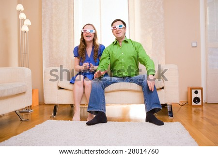 Happy couple at home watching movie in 3D glasses. - stock photo