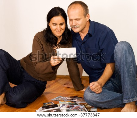 Happy couple at home with photo album