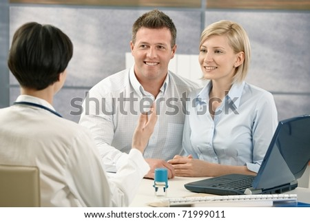 Happy couple at medical appointment, talking to doctor, smiling.? - stock photo