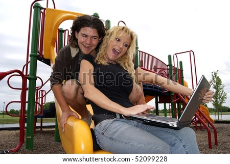 Happy couple at playground with laptop - stock photo