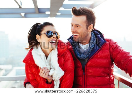 Happy couple at roof top hugging and laughing - stock photo