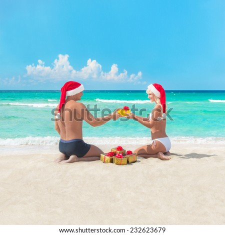 Happy couple at sea beach in santa hats give presents for each other - christmas or new year holidays in hot countries concept - stock photo