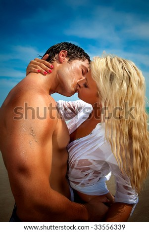 Happy couple at the beach kissing.