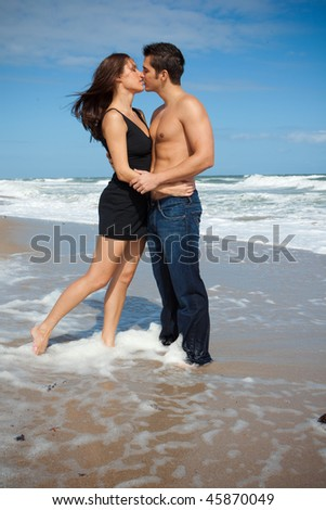 Happy couple at the beach, kissing. - stock photo