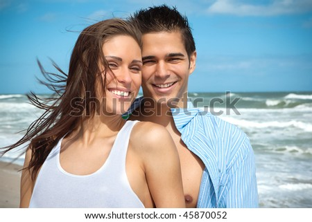 Happy couple at the beach, smiling, looking into camera - stock photo
