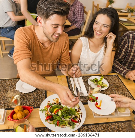 Happy couple at the restaurant and being served of food in the plate - stock photo