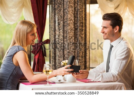 Happy couple at the restaurant, girl is giving present to her boyfriend - stock photo