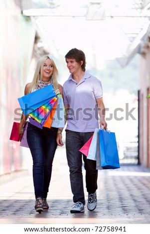 Happy couple at the shopping center with bags - stock photo