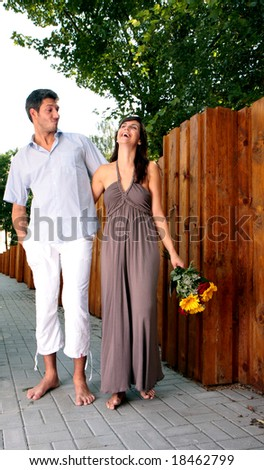 Happy couple at wall walk promenade with flowers bouquet - stock photo
