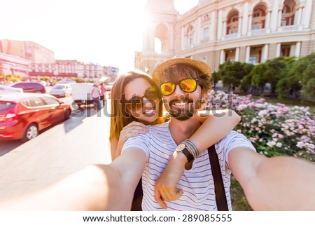Happy couple, attractive woman and man walking  in city and  enjoying romance. Lovers making selfie, smiling and have fun together. Odessa, Ukraine. - stock photo