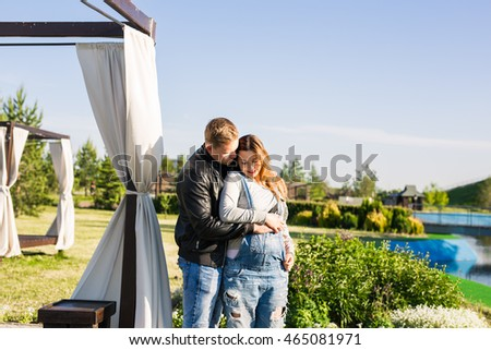 Happy couple awaiting baby, cute pregnant woman with husband enjoying spring weather, love concept