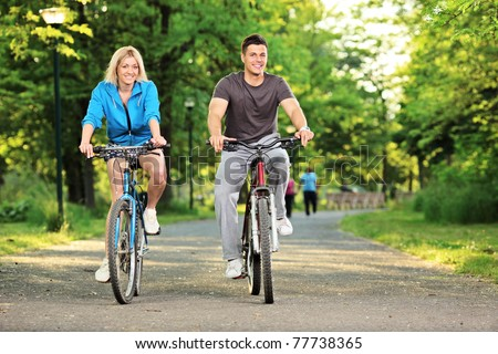 Happy couple biking in the city park, Skopje, Macedonia - stock photo