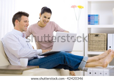 Happy couple browsing internet at home, using laptop computer, sitting on couch, smiling.