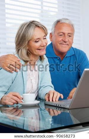 Happy couple browsing internet together on laptop - stock photo