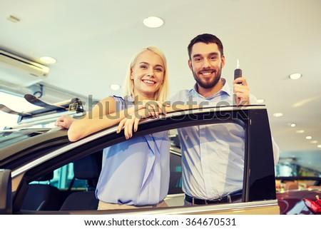 happy couple buying car in auto show or salon - stock photo