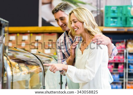 Happy couple buying food in supermarket - stock photo