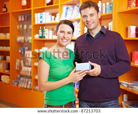 Happy couple buying some medicine in a pharmacy