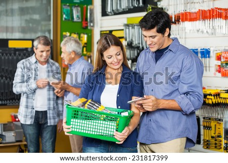 Happy couple buying tools at hardware store with customers in background - stock photo