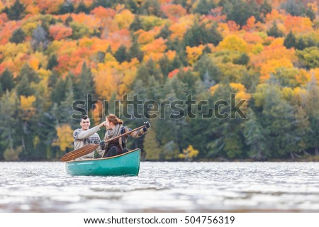 Happy couple canoeing in a lake in Canada. Many trees on background with colourful leaves during autumn. They are young and happy, enjoying a canoe trip together. Wanderlust and nature concepts.