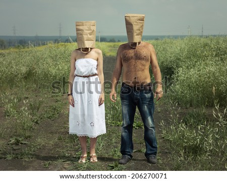 Happy couple carrying a shopping paper bag on head - stock photo