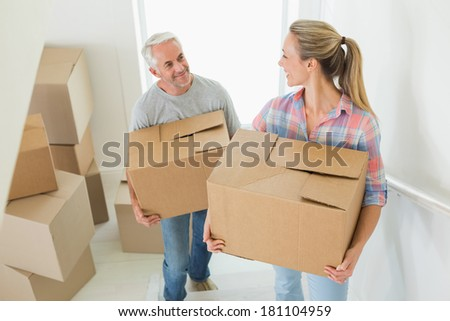 Happy couple carrying cardboard moving boxes in their new home - stock photo