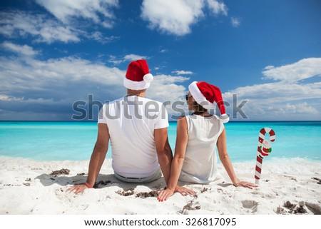 Happy couple celebrating Christmas on beach - stock photo
