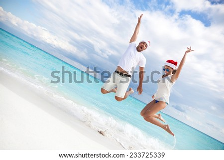 Happy couple celebrating Christmas on beach, jumping in the air - stock photo