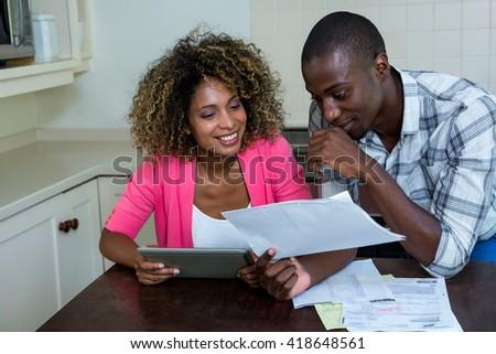 Happy couple checking bills while using digital tablet in kitchen