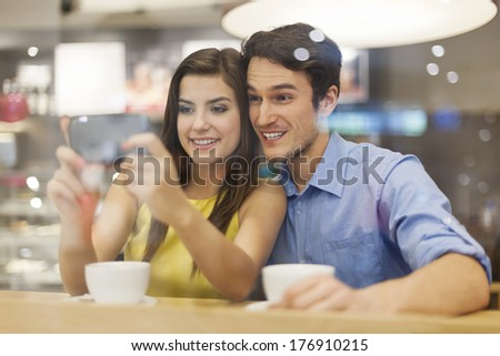 Happy couple checking something on mobile phone in cafe   - stock photo