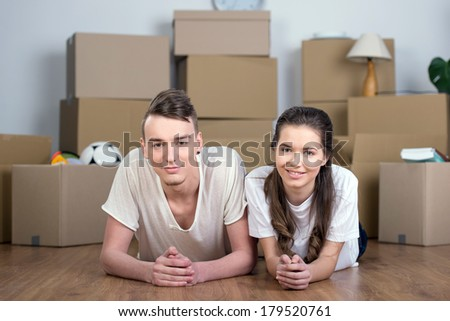 Happy couple. Cheerful middle-aged couple lying together between cardboard box stacks and smiling - stock photo