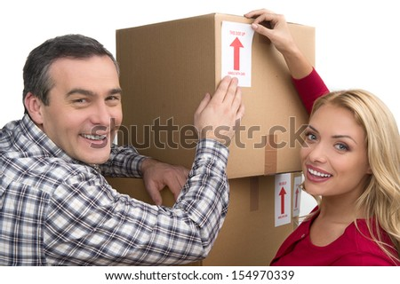Happy couple. Cheerful middle-aged couple lying together between two cardboard box stacks and smiling  - stock photo