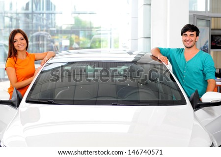 Happy couple chooses to buy a car in showrooms - stock photo
