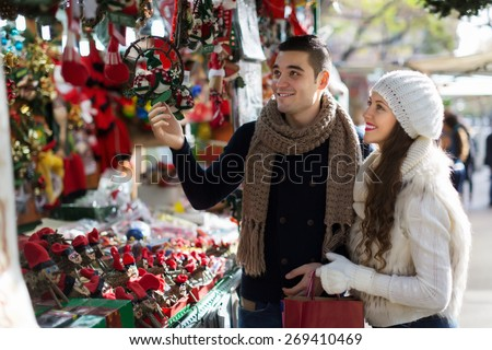 Happy  couple  choosing Christmas souvenirs at Barcelona - stock photo