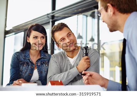 Happy couple choosing new home project with architect - stock photo