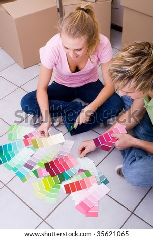 happy couple choosing paint color for new home - stock photo