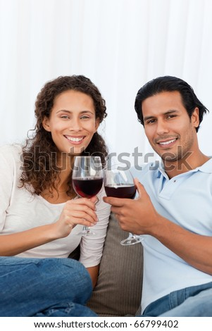 Happy couple clinking glasses of red wine on the sofa in the living-room - stock photo